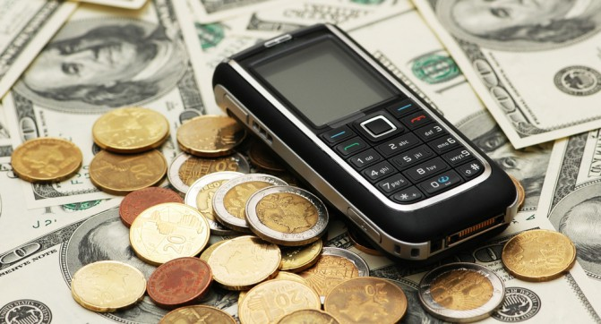 Mobile phone with coins and dollar bank notes